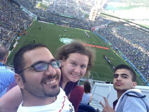 Smith, Iraqi adult mentor Mustafa Mohammed, and student Aria Qadir at a Seattle Sounders match.